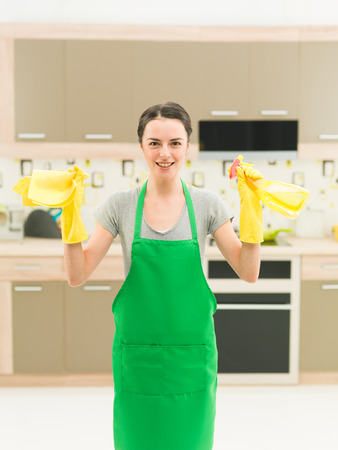 housewife gloves: portrait of happy caucasian woman standing in kitchen and holding cleaning products Stock Photo