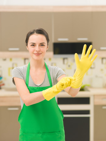 housewife gloves: happy housewife putting on rubber gloves with home kitchen background