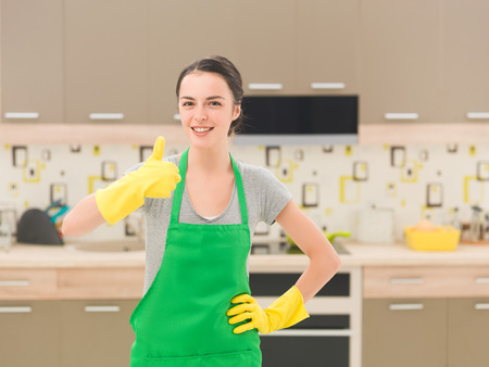 cleaning woman happy and excited standing in kitchen, showing thumb up