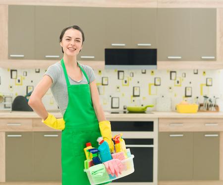 productos de limpieza: joven feliz de pie femenino cauc�sico en la cocina sosteniendo productos de limpieza