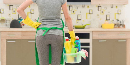 back view of cleaning lady standing in kitchen holding bucket with cleaning products