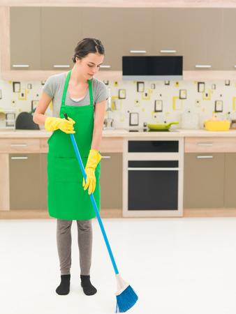 youn caucasian woman standing in kitchen, sweeping floor with broom Stock Photo
