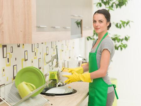 young beautiful caucasian woman washing dishes Stockfoto
