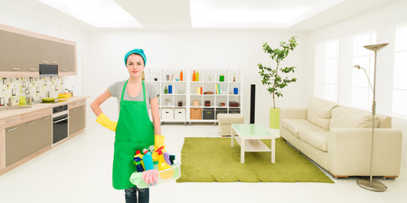 housecleaning: young caucasian woman standing in clean house holding cleaning products