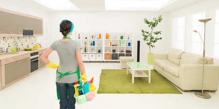 young caucasian woman standing in clean house holding cleaning products, looking at tidy room Stockfoto