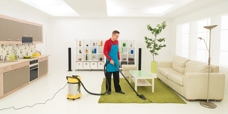 caucasian man cleaning carpet with vacuum cleaner in living room