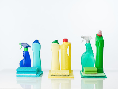sanitizing: household cleaning supplies arranged by color, on white background