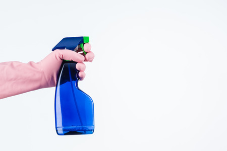 human hand with protective glove holding cleaning spray bottle. isolated on white 免版税图像