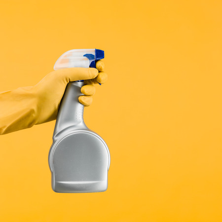 cleaning supplies: hand with rubber glove holding cleaning spray container on yellow background Stock Photo