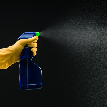 hand with rubber glove holding cleaning bottle and spraying liquid, on black background Фото со стока
