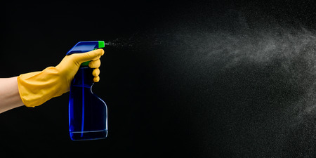 hand with rubber glove holding cleaning bottle and spraying liquid, on black background Stockfoto