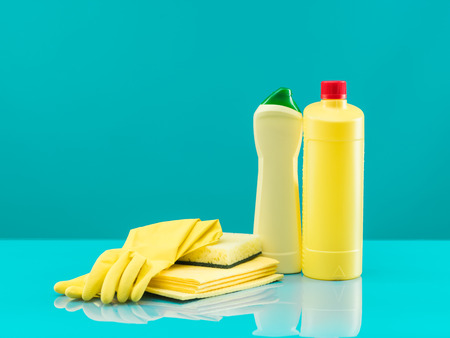rags: group of yellow cleaning tools on table with blue background Stock Photo