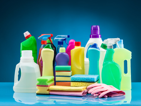 cleaning products and supplies on table with blue background