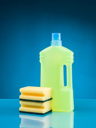 desinfectante: botella de detergente líquido y esponjas sobre fondo azul Foto de archivo