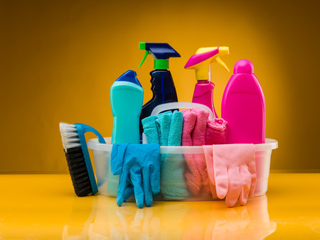 cleaning: cleaning products and utensils in plastic basin against yellow background Stock Photo