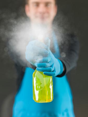 schoonmaak werknemer spuiten vloeibaar wasmiddel op raamoppervlak voor hem
