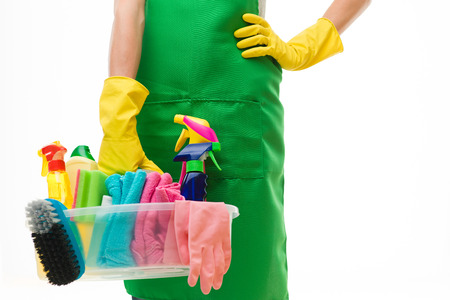 close-up of caucasian cleaning lady holding basin with cleaning supplies, against white background