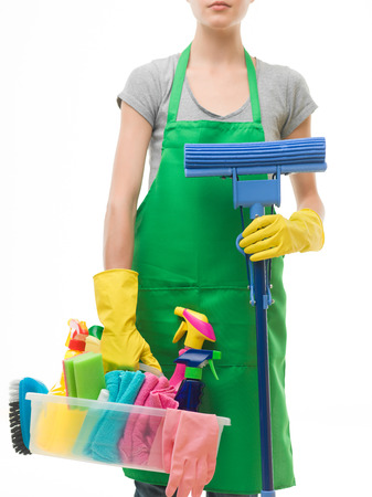 caucasian woman wearing apron and holding cleaning supplies and mop, on white background