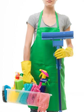 mujer de raza caucásica con el delantal y la celebración de productos de limpieza y la fregona, sobre fondo blanco