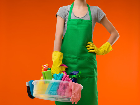 house maid: close-up of maid holding cleaning supplies, on orange background