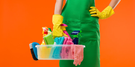 productos de limpieza: primer plano de la señora de la limpieza que sostiene suministros, sobre fondo naranja