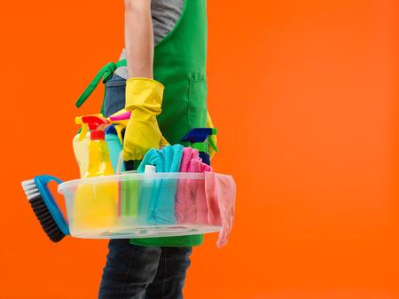 productos de limpieza: vista lateral de la mujer caucásica de pie y con los productos de limpieza, preparándose para el trabajo Foto de archivo