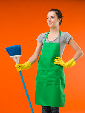house maid: happy cleaning lady standing and holding broom, on orange background