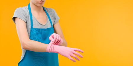 caucasian cleaning woman putting up rubber gloves on hands, on yellow background