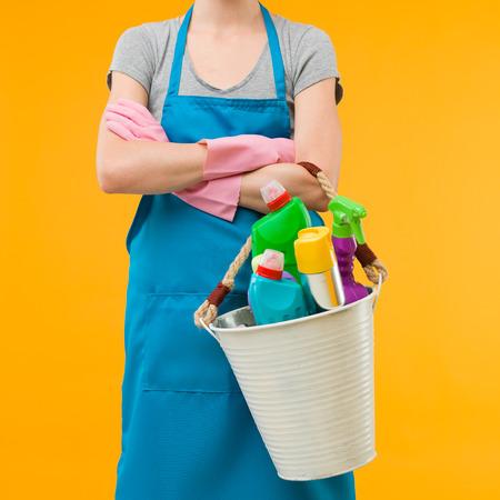 vrouw in blauwe schort met metalen emmer met schoonmaak leveringen tegen gele achtergrond