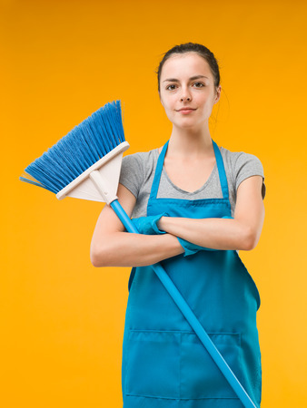 house maid: happy caucasian woman standing with arms crossed and holding a broom, on yellow background Stock Photo