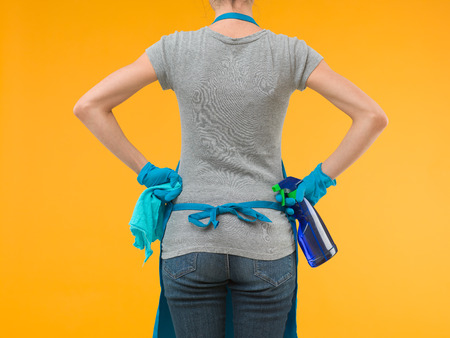 wash cloth: back view of woman holding cleaning equipment and looking in front of her, on yellow background Stock Photo