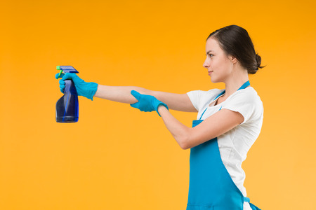 side view of cleaning woman pointing spray with liquid detergent, shooting, against yellow background