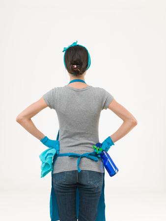 espalda: Volver la vista de raza cauc�sica mujer de la limpieza de pie y la celebraci�n de los productos de limpieza contra el fondo blanco