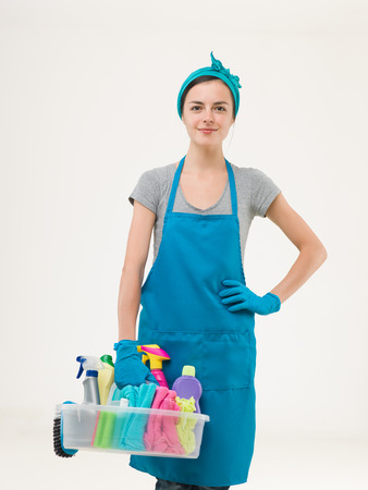 youn beautiful maid standing and holding cleaning supplies getting ready for work. isolated on white background Standard-Bild