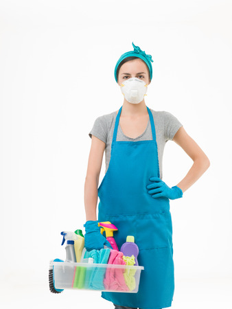 young woman wearing protection mask and holding basket with cleaning supplies, on white background