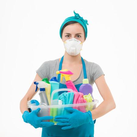 productos quimicos: Ama de casa joven que llevaba máscara de protección, la celebración de los productos de limpieza contra el fondo blanco