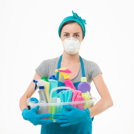 young housewife wearing protection mask, holding cleaning supplies against white background Stockfoto