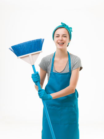 house maid: happy cleaning lady standing, holding broom and laughing. isolated on white background