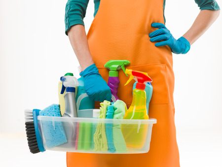 close-up of caucasian woman holdinh basin with cleaning supplies, on white background