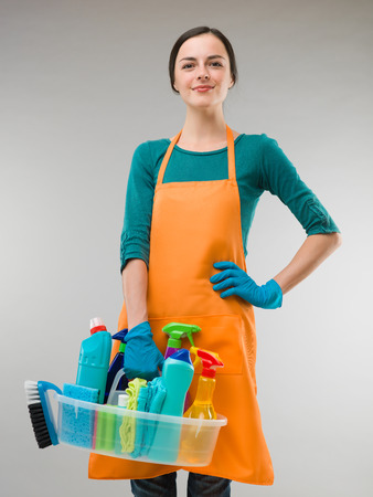 productos quimicos: mujer feliz celebración de equipo de limpieza y mirando de frente a la cámara, sobre fondo gris Foto de archivo