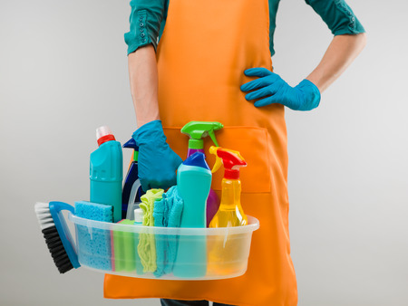 everyday jobs: close-up of caucasian woman holding basin with cleaning supplies