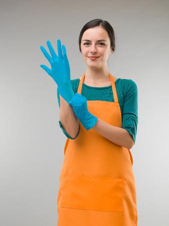 wash dishes: joven mujer de la limpieza feliz de ponerse los guantes de goma