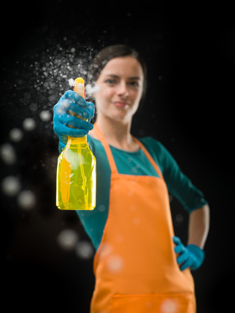 cleaning window: portrait of cleaning woman aiming spray bottle in front of her, on black background