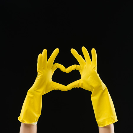 hands in yellow rubber gloves making heart shape with fingers, on black background