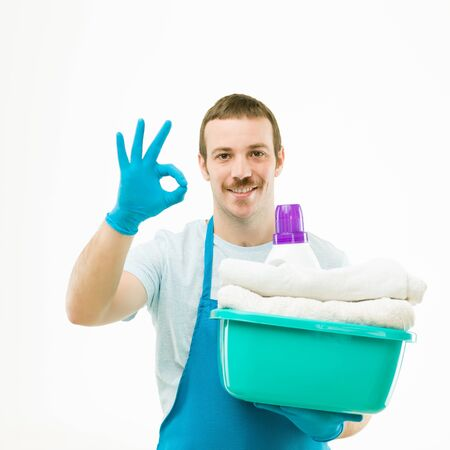 man laundry: portrait of caucasian man holding basket with laundry, smiling and showing ok sign, on white background