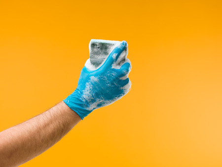 household tasks: male hand with protective glove holding sponge with detergent and foam, against yellow background Stock Photo