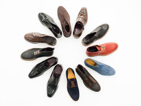 bovenaanzicht, diverse mannelijke schoenen die in cirkel, geïsoleerd op een witte achtergrond