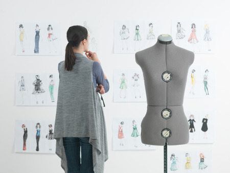 successful female fashion designer looking at drawings in her studio Standard-Bild