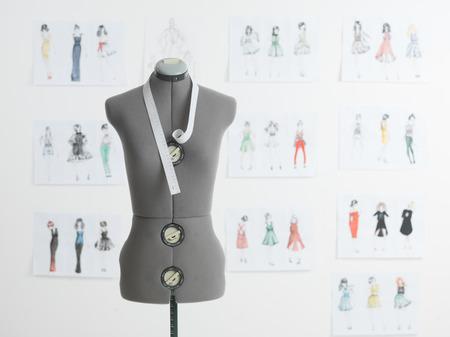 couturières professionnelles mannequin avec un ruban à mesurer, de croquis de mode sur le mur derrière Banque d'images