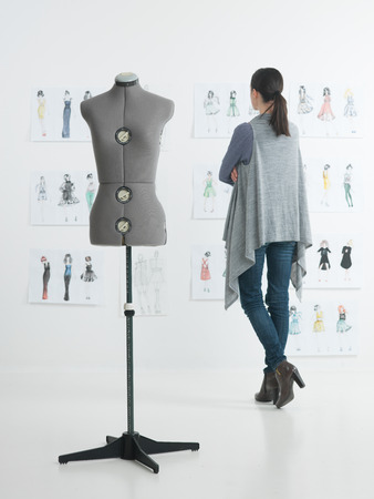 female fashion designer standing in her studio looking at sketches